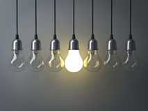One hanging light bulb glowing different and standing out from unlit incandescent bulbs Stock Photo