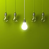 One hanging light bulb glowing different and standing out from unlit incandescent bulbs with reflection on green background. Leadership and different business Stock Image