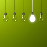 One hanging light bulb glowing different and standing out from unlit incandescent bulbs. With reflection on green background , leadership and different business Royalty Free Stock Photo