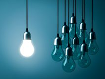 One hanging light bulb glowing and standing out from unlit incandescent bulbs Royalty Free Stock Photos