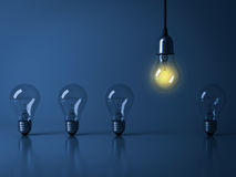 One hanging light bulb glowing from unlit incandescent bulbs on dark blue background with reflection Stock Photos