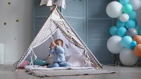 One happy cute baby jerking a garland in a children`s tent. The child has played enough stock footage