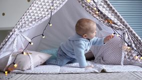 One happy cute baby playing with a garland in a children`s tent. A little boy is crawling inside a children`s tent stock video footage