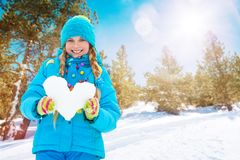 One happy girl with heart made of snow. Beautiful happy girl holding big heart made of snow standing outside in the forest Stock Image