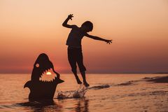 One happy little boy playing on the beach at the sunset time. Royalty Free Stock Photos