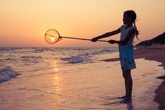 One happy little girl playing on the beach at the sunset time. Stock Image