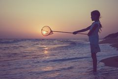 One happy little girl playing on the beach at the sunset time. Royalty Free Stock Image