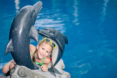 One  happy little girl playing near swimming pool at the day tim. E.  Child having fun outdoors. Concept of   summer vacation Stock Photo