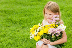 One happy little girl sitting on the grass with a bouquet of flo Royalty Free Stock Images