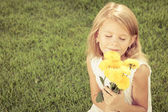 One happy little girl sitting on the grass with a bouquet of flo Stock Image