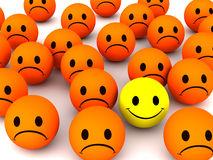 One happy smiley. A happy smiley amongst many sad ones in orange color Royalty Free Stock Images
