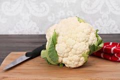 One head of Cauliflower Head on a Cutting Board. One fresh, healthy head of cauliflower on a cutting board Royalty Free Stock Photography