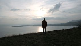 Man alone walking on the hill to sea at sunset. One hiker enjoying vacation in the wild area around mount and coast. Seaside, good feelings, emotional concept of stock video