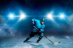 One hockey player on ice, spotlights on background royalty free stock photos
