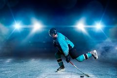 One hockey player skating on ice arena. A hockey player skating on ice arena, spotlights on black background. Male person in helmet, gloves and uniform holds stock photography