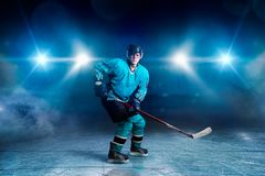 One hockey player skating on ice arena. Spotlights on black background. Male person in helmet, gloves and uniform holds stick in hands royalty free stock image