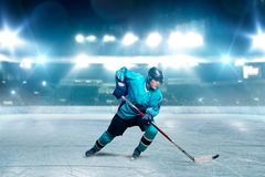 One hockey player skating with stick on ice arena stock photo