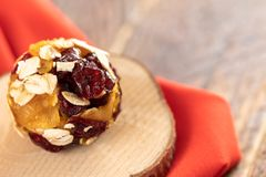 One homemade energy ball made from pieces of dried fruits on wooden saw cut on red fabric. Close-up one healthy homemade energy ball made from pieces of dried stock images
