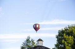 One hot air trying to get to the drop spot. Hot air balloon in flight Hot air balloons shaped like bees Hot air balloon shaped as the Abbey of Saint Gall A hot royalty free stock photo