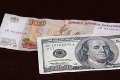One hundred american dollars banknote above russian one hundred rubles. One hundred american dollars banknote is above russian one hundred rubles on black stock photography