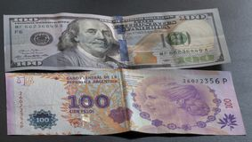 One hundred argentine pesos and one hundred dollars. stock image