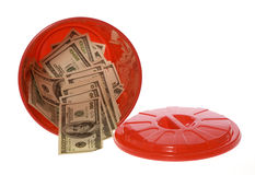 One Hundred  Bills in Garbage Can. US Currency Throwing Money Away: One Hundred Dollar Bills inside of a red garbage can with a lid next to it.   isolated on Royalty Free Stock Photos