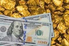 One hundred dollar banknotes on gold mine close up. Mining industry concept with dollars and gold.  Royalty Free Stock Images