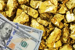 One hundred dollar banknotes on gold mine close up. Mining industry concept with dollars and gold royalty free stock photo