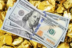 One hundred dollar banknotes on gold mine close up. Mining industry concept with dollars and gold stock photo
