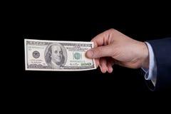 One hundred dollar bill. Businessman hand holding one hundred dollar bill (isolated on black Stock Photo