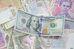 One hundred dollar bill on the background of ukrainian hryvnia. Stock Photography