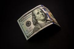 One hundred dollar bill on black reflective background stock images