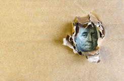 Franklin portrait on a hundred dollars bank note through the hole. One hundred dollar bill concept. Franklin portrait on a hundred dollars bank note through the stock photos