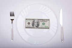 One hundred dollar bill lies on white plate. With knife and fork on opposite sides Royalty Free Stock Photos