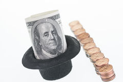 One hundred dollar bill and one hundred pennies. One hundred dollar bill in a hat and one hundred pennies close-up Stock Photography