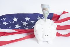 One hundred Dollar bill in piggy bank on American flag. Background Royalty Free Stock Image