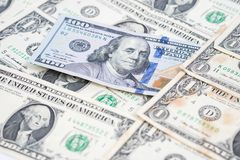 One hundred dollar bill in pile of one dollar banknotes. Leadership and different concept with unique one hundred banknote on one dollar bills. Financial and Royalty Free Stock Image