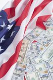 One hundred dollar bills on American flag. Background Royalty Free Stock Photos