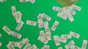 One hundred dollar bills are falling against a green background. Great use for money and finance related concepts stock video footage