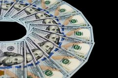 One hundred dollar bills are fanned out on a black background. Top side view.  royalty free stock images