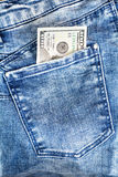 One hundred dollar bills in jeans pocket. One hundred dollar bills in blue jeans pocket stock images