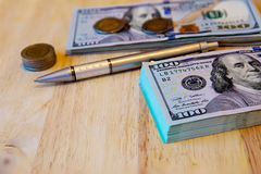 One hundred dollar bills, thai coins and pen on the old wooden. One hundred dollar bills and pen on the old wooden.Business concept - money, pen and cash .The Stock Photos
