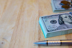 One hundred dollar bills, thai coins and pen on the old wooden. One hundred dollar bills and pen on the old wooden.Business concept - money, pen and cash .The stock photography