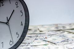 One hundred dollar bills and a white big clock, concept, time is money background stock images