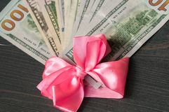 One hundred dollar bills wrapped in a pink ribbon royalty free stock images