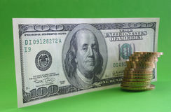One hundred dollar note with coins Stock Photos