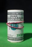 One hundred Dollar roll tightened red rubber band Stock Photography