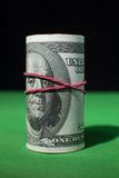 One hundred Dollar roll tightened red rubber band. One hundred Dollar roll tightened with red rubber band. . Green black background. Franklin looks at you Stock Photo