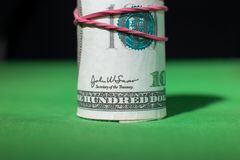 One hundred Dollar roll tightened red rubber band. One hundred Dollar roll tightened with red rubber band. . Green black background. Franklin looks at you Royalty Free Stock Images