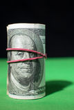 One hundred Dollar roll tightened red rubber band Royalty Free Stock Image